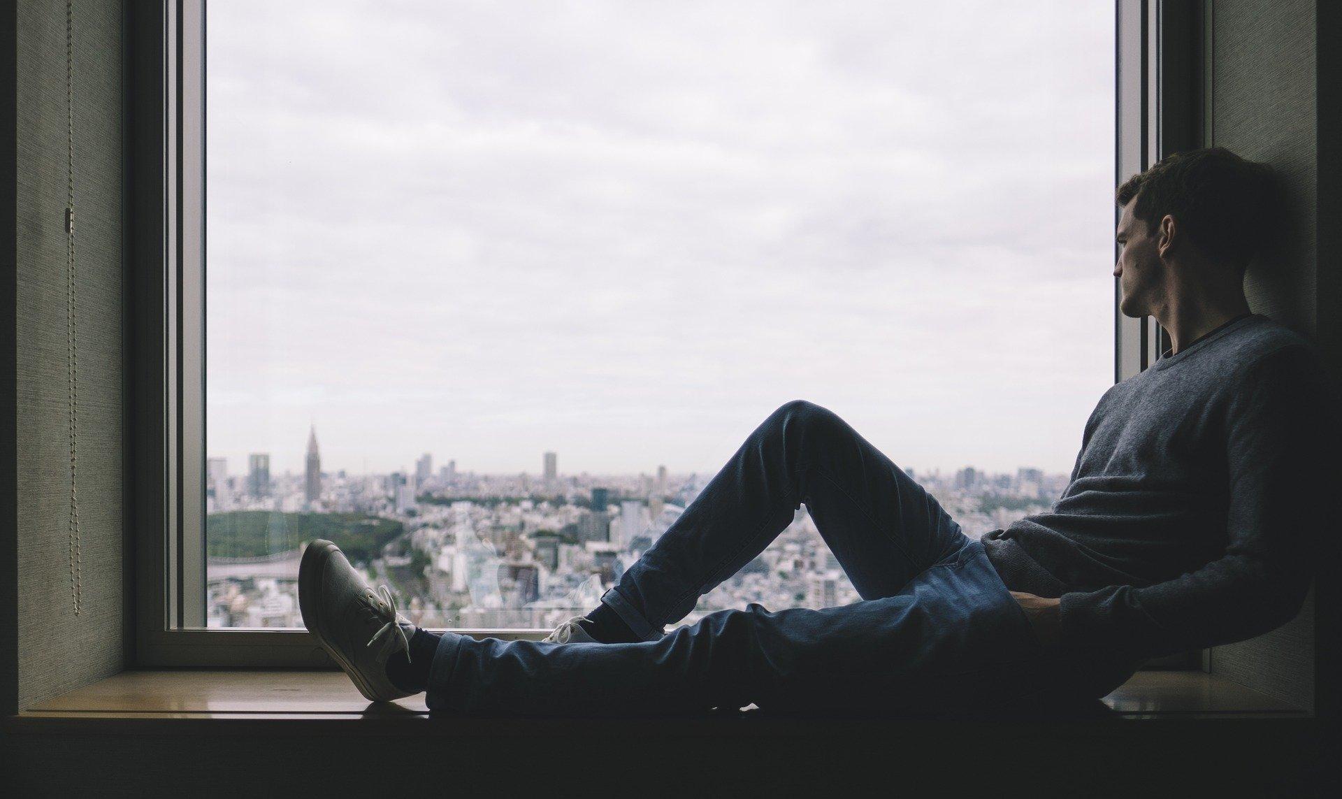 Mann am Fenster, der über eine Stadt blickt