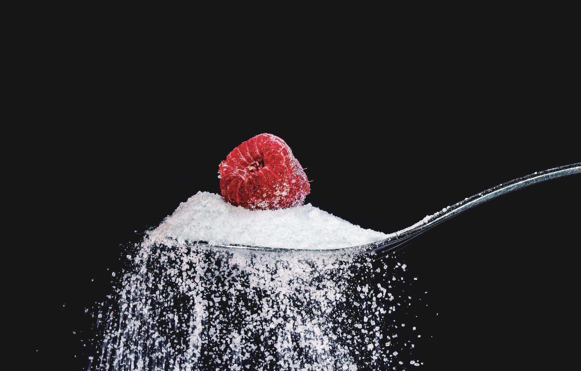 Zucker und Himbeere auf Löffel