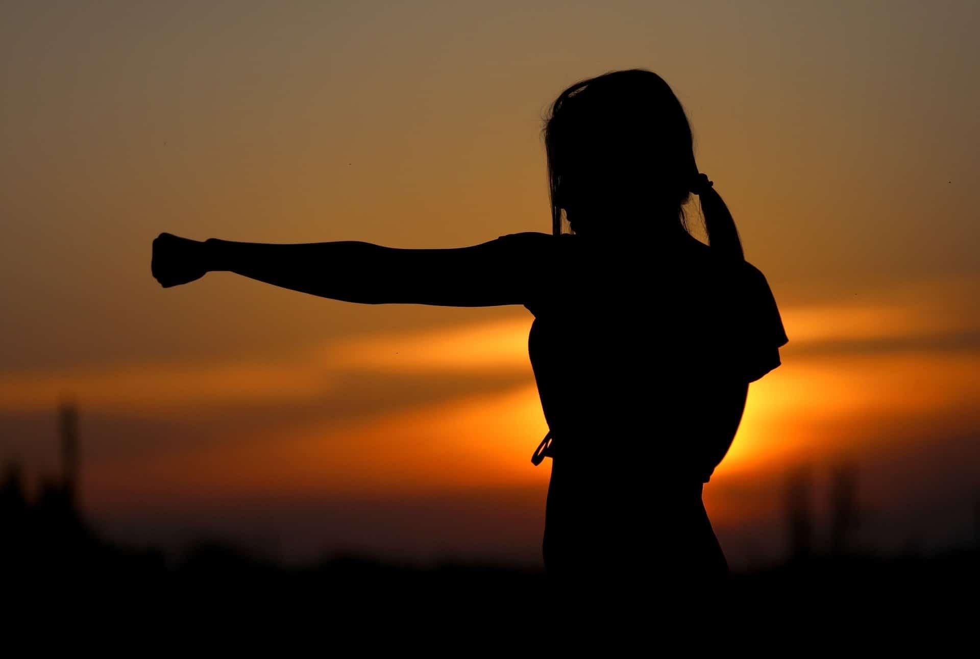 Frau boxt im Sonnenuntergang