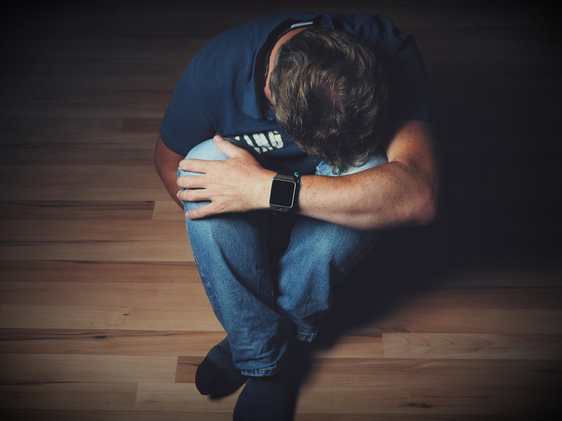 Mann sitzt in Abwehrhaltung auf dem Boden
