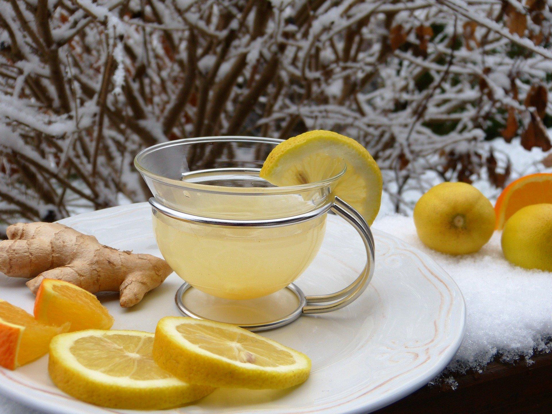 Ingwertee mit Zitrone auf einem Teller im Schnee