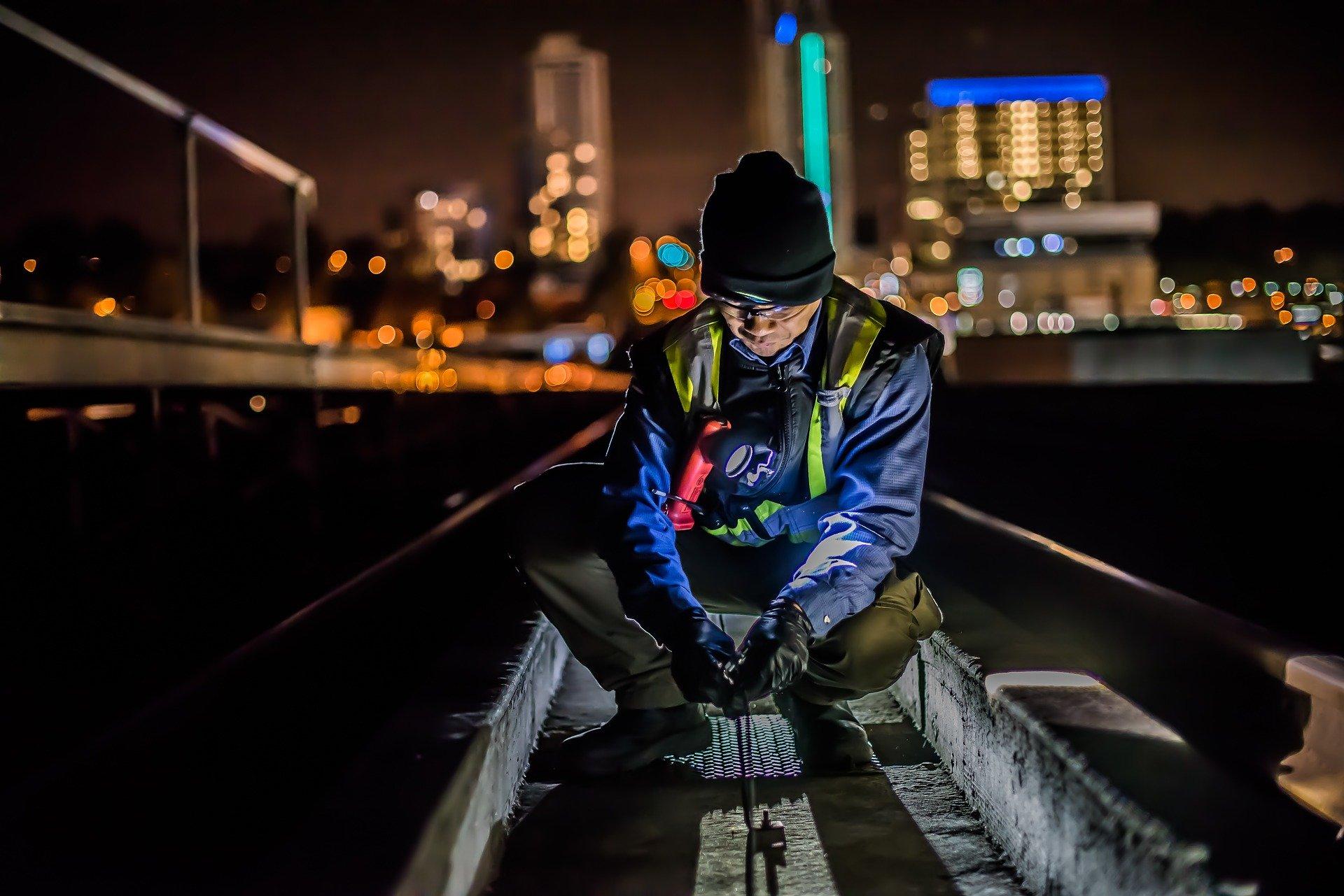 Mann arbeitet nachts auf Gleisen