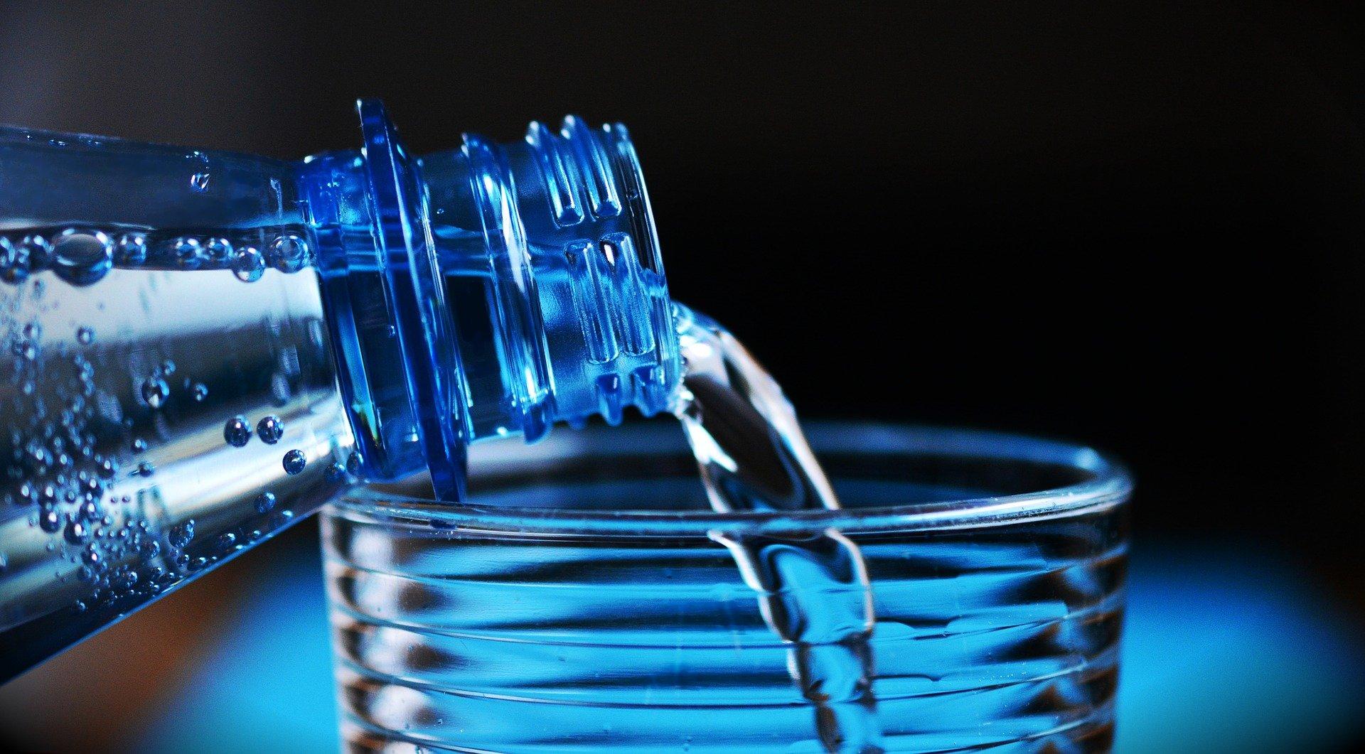 Sprudel, der in ein Wasserglas gegossen wird