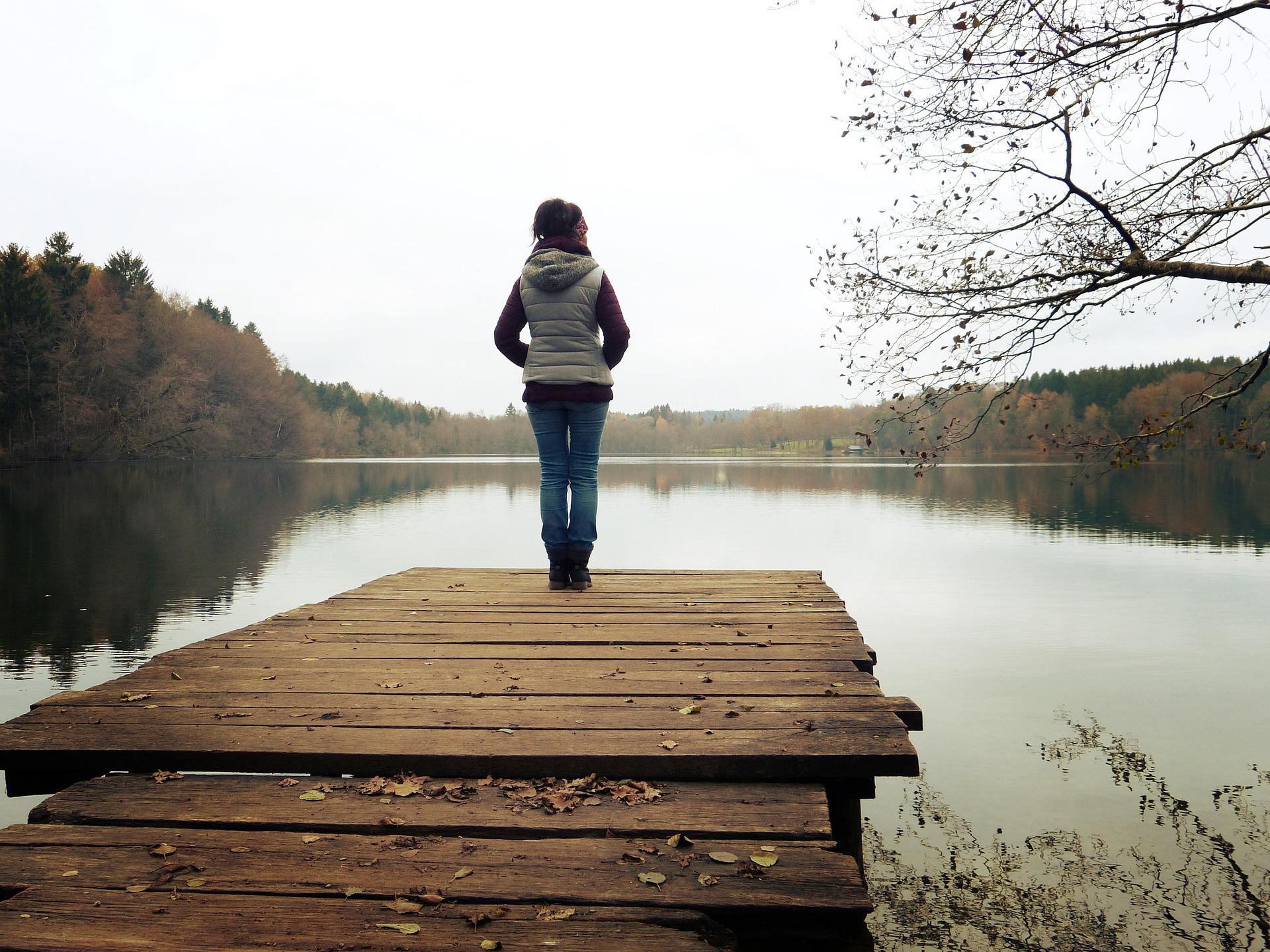 Frau steht alleine auf Holzsteg am See